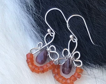 The Emma earring: hand formed sterling silver wire with a purple tourmaline  teardrop bead and a string of orange carnelian stone beads