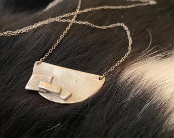 """The """"Adrian"""" necklace of a half circle with three rectangles layered up on the necklace pendant"""