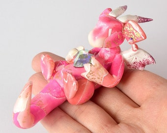 Pink and white watercolor-style heart dragon, bright pink dragon holding a heart, cute handmade dragon sculpture, Valentine's Day figurine