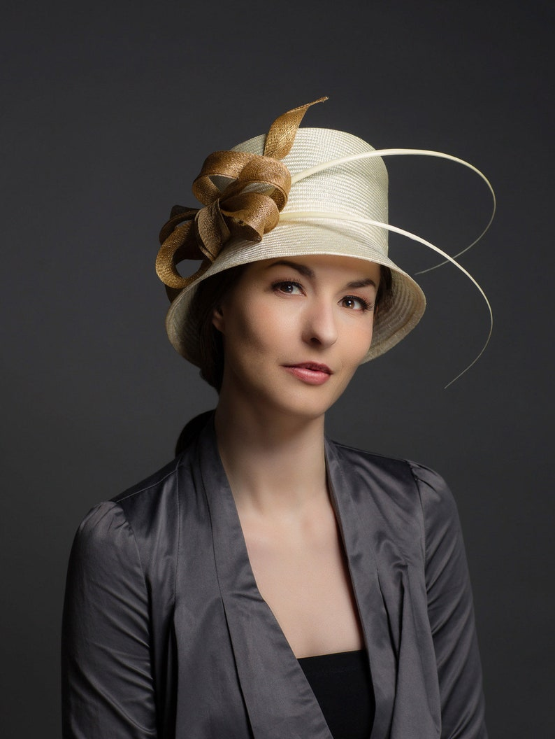 328746f01 Cream straw cloche hat with gold ribbon detailing and ivory quills.  Melbourne cup races hat, Mother-of-the-bride hat or summer wedding hat