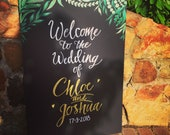 Welcome chalkboard sign with foliage
