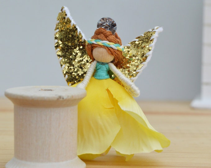 Miniature  flower fairy doll with golden wings.