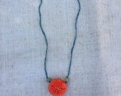 Necklace with big, bright orange shibori silk ball strung on thunder-blue silk ribbon.