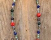Necklace on silk cord with shibori hand-stitched balls and glass beads.