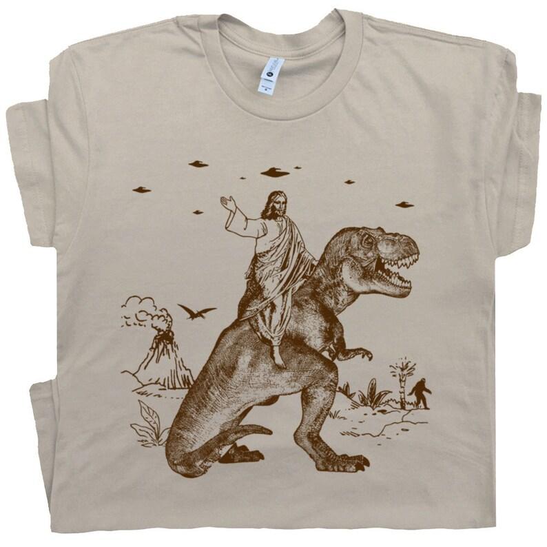 f201457d5 Jesus Riding Dinosaur T Shirt UFO T Shirt Offensive T Shirt | Etsy