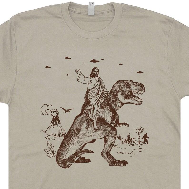 cf9e5a1125e Jesus Riding Dinosaur T Shirt UFO T Shirt Offensive T Shirt