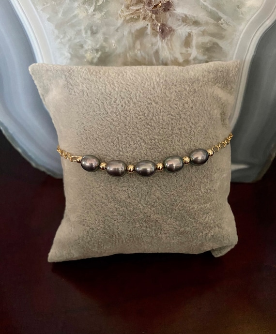 Freshwater black pearl bracelet with 14k yellow gold filled beads and oval diamond cut link chain.