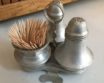 Vintage aluminum salt and pepper shakers, and toothpick cup in caddy.