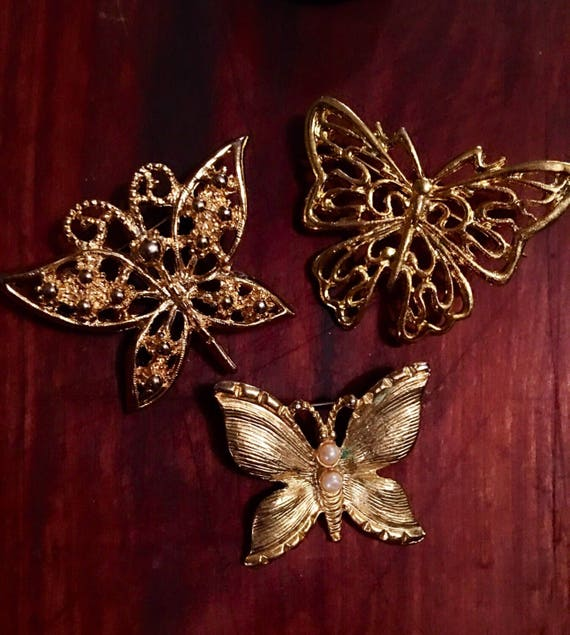 Grouping of Threes golden butterfly brooches