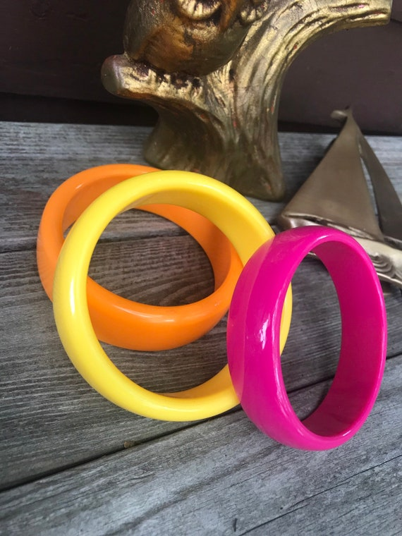 A grouping of 3 Cheerful Resort Citrus Rainbow Colored Plastic Bangle Bracelets
