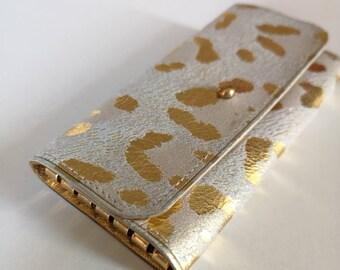 Porte-clés en cuir léopard doré sur fond gris/beige