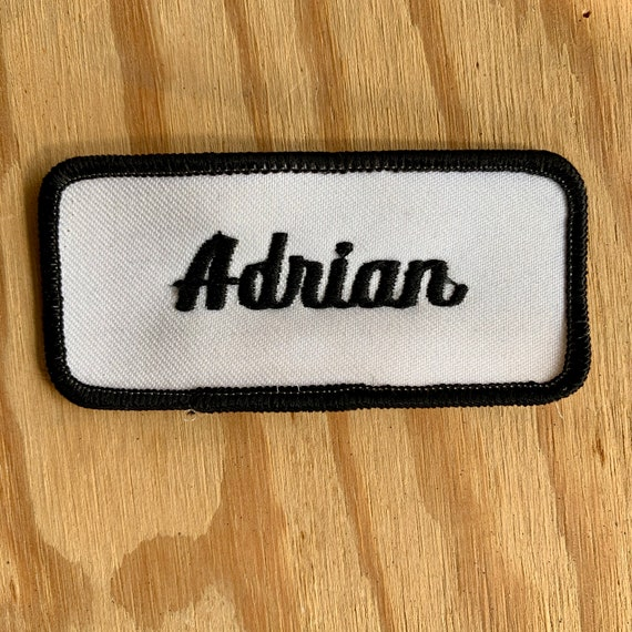 "Adrian. A white work shirt patch that says ""Adrian"