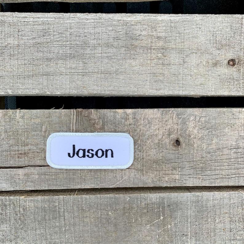 A white work shirt name patch that says Jason in print script Jason