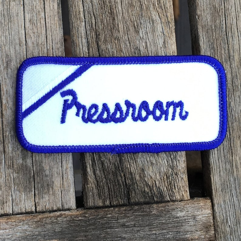 Pressroom A white work shirt uniform patch that says Pressroom in blue script with blue border.