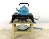 Antique doll cooker stove with tea candle on tin table with enamel dishes