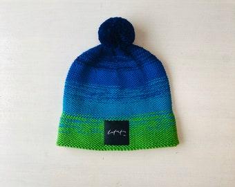 """S izmērs (54-56cm) - zili zaļa merīnvilnas  cepure  ar """"Latvietis"""" logo - Gatava sūtīšanai"""