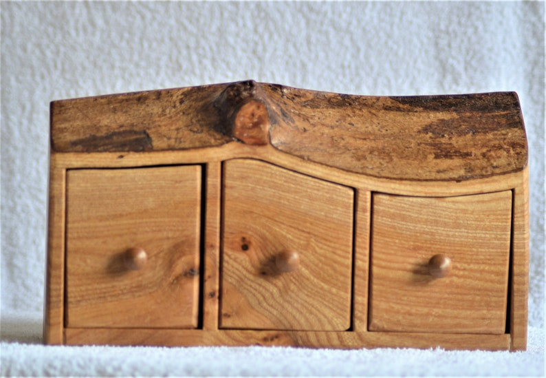 A Rustic three drawer boxchest cut from a solid Elm log with feature bark edge.