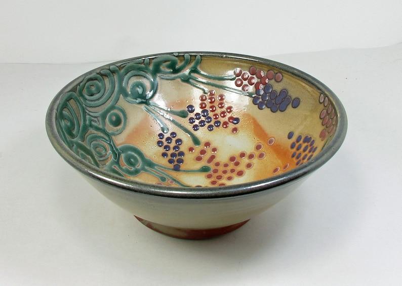 bol de service en céramique dans le shino avec des fleurs pourpres et rouges