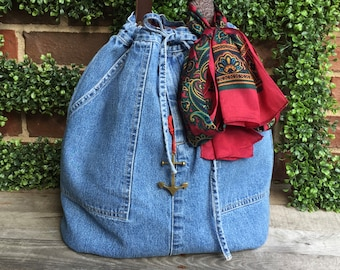 Recycled jeans drawstring hobo tote with inside pockets and brass grommets