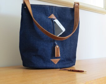 Hobo or bucket bag in denim and vegan leather with hidden front pocket and inside pockets