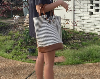 Slouch bag in navy pinstripe with tobacco leather base and wooden handle