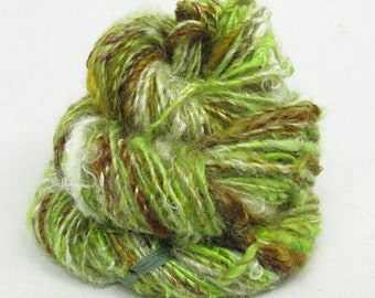 Handspun Single, from Kid Mohair dyed shades of chartreuse and brown, with natural locks added.