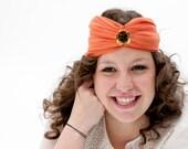 Dundee - Turbante naranja hecho con sinamay de seda y detalle de flor dorada