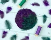 Tocado redondo con plumas moradas y verdes