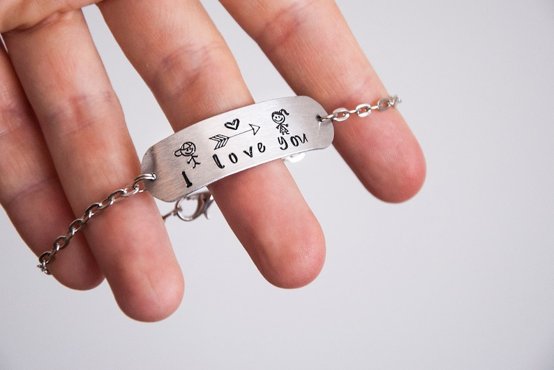 a arrow Bracelet with engraved metal tag with a cute boy and a girl a heart and the  I love you  lettering handmade romantic gift ideas