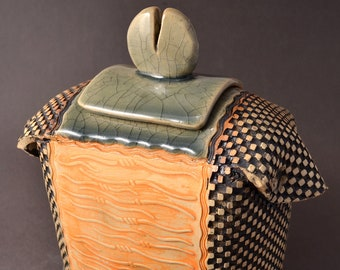 Sculptural Samurai Jar with lid, Rubbed back black and tangerine stain, Crazed Celadon glaze inside, on the lid, and on the foot and base.