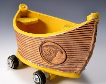 Small Stoneware Dory Boat with Wheels Turmeric Yellow glaze inside and rustic red-brown stained outside with raven image