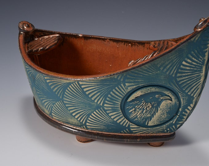 """Medium """"Dory"""" Shaped Long Serving bowl with Ancient Copper glaze and textured exterior with raven image by Tom Bottman"""
