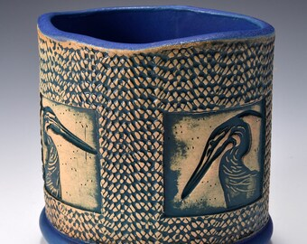 Oval Desktop Pencil and Pen holder in matte dark blue Glaze and Lively Textured Exterior with blue heron Image by Tom Bottman