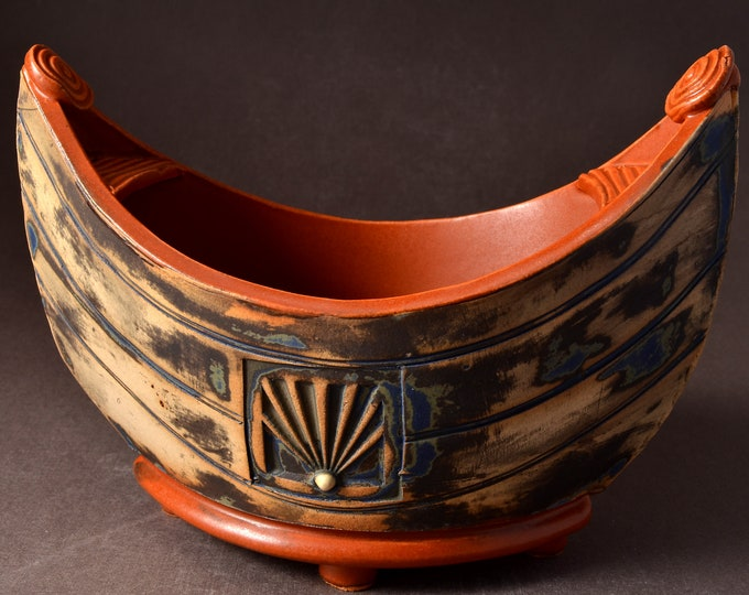 "Small ""Elven Boat"" shaped bowl with paprika red glaze inside and Red Brown stained outside with medallion and inset colored clay dot"