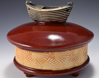 Sculptural Stoneware Jar with Little Boat Knob on the lid, Rubbed back ambrosia yellow stain, gloss firebrick red glaze by Tom Bottman