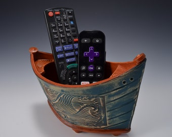 """Small """"Elven Boat"""" shaped bowl with paprika red glaze inside and rustic weathered looking stained outside with crashing wave pattern"""