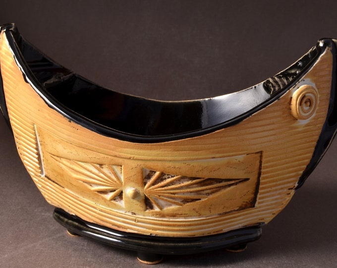 """Small """"Elven Boat"""" shaped bowl with gloss black glaze inside and Yellow Brown stained outside with medallion and inset colored clay dot"""