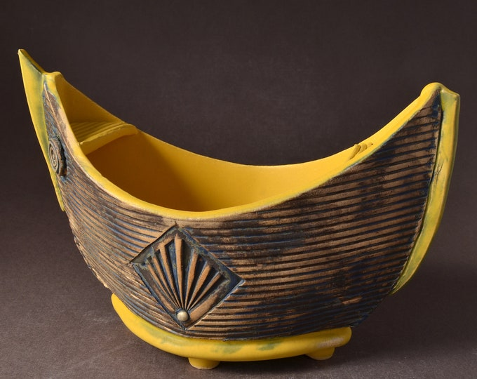 """Small """"Elven Boat"""" shaped bowl with turmeric yellow glaze inside and Red Brown  stained outside with medallion and inset colored clay dot"""