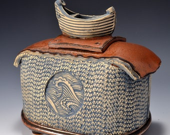 Sculptural Stoneware Jar with Boat Knob on the lid, Rubbed back yellow and blue-green stain, crashing wave image