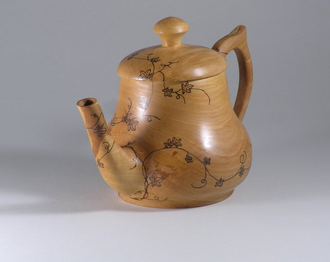 Wood teapot with a vine design