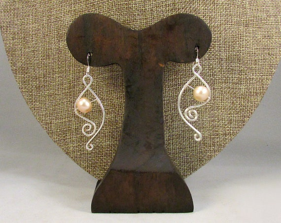 Pink pearl earrings with silver swirls