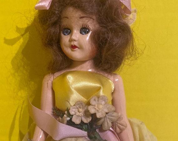 Vintage hard plastic doll in yellow dress
