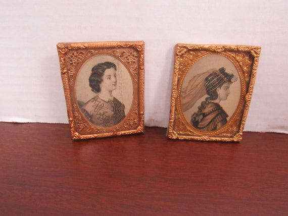 Miniature pair of metal picture frames with prints