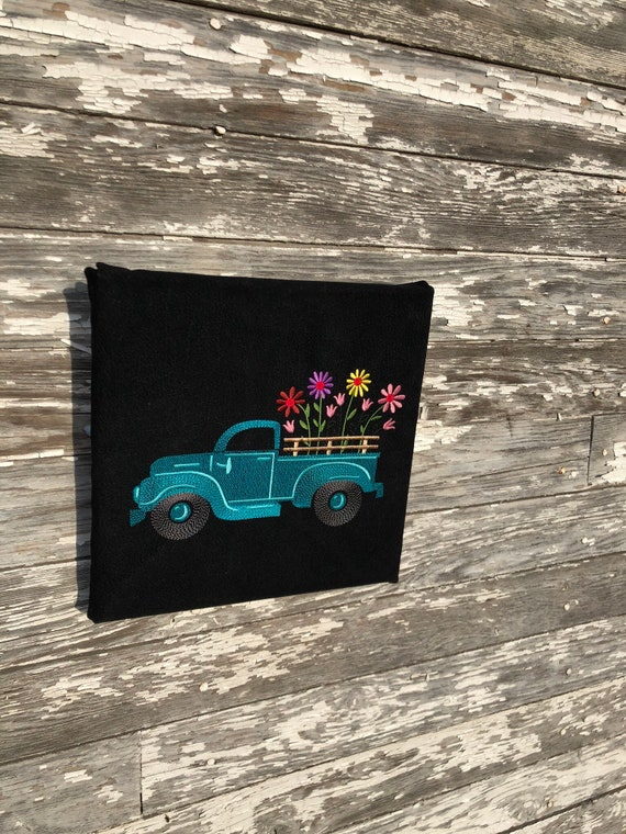 Machine embroidery picture of vintage truck with flowers on canvas and black textured fabric