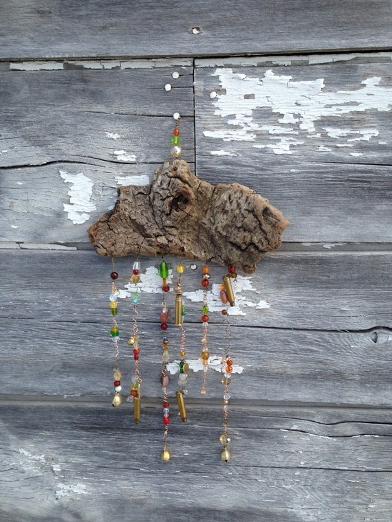 Flathead lake driftwood sun catcher with brass and cooper wire . Brass gun shells and glass and natural beads