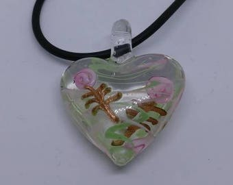 Glass heart pendant necklace on black cord with extension chain.  Green swirls and flowers.