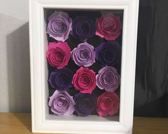 White shadow box with pink and purple paper flowers
