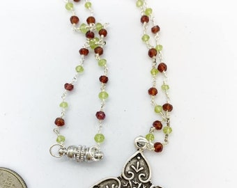 18 inch Garnet and peridot rosary style chain with pewter pendant and magnetic clasp.