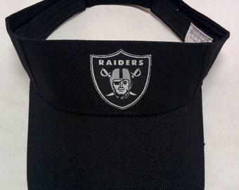 Oakland Raiders Heat Applied Applique on a Black team color Visor hat cap! Adjustable strap. Fits everyone!