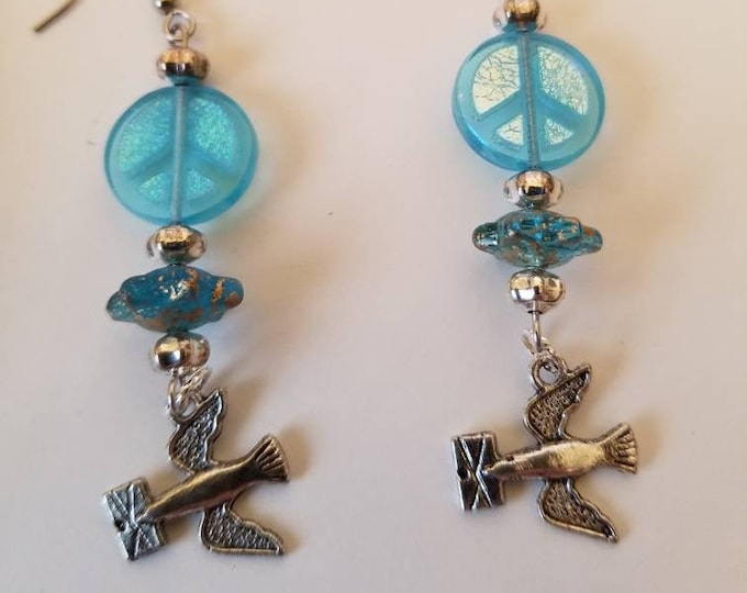 Earrings, doves and peace. Iridescent blue glass peace symbols, silver colored accent beads and speckled glass flying saucer beads.
